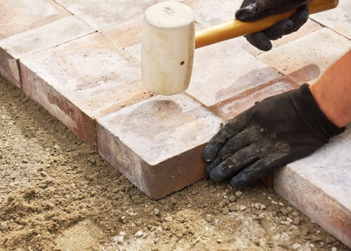 hands installing brick pavers